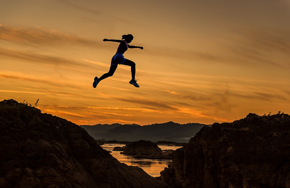Woman Jumping Across Rocks